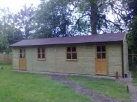 9m x 3m Workroom with garden office doors and windows and a felt tile roof. Internally split with a partition.